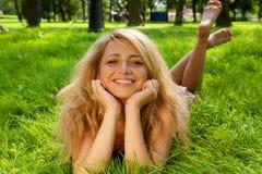 Giovane donna sorridente sull'erba Fotografia Stock Libera da Diritti