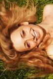 Giovane donna sorridente sull'erba Immagini Stock