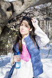 Giovane donna sorridente in un'acqua potabile della montagna di inverno Fotografie Stock Libere da Diritti
