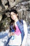Giovane donna sorridente in un'acqua potabile della montagna di inverno Immagine Stock
