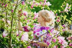 Giovane donna sotto l'albero di fioritura della magnolia un giorno di molla Fotografia Stock
