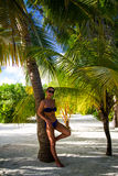Giovane donna sotto la palma alla spiaggia tropicale Fotografie Stock
