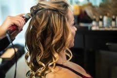 Giovane donna splendida che ottiene capelli arricciati immagini stock
