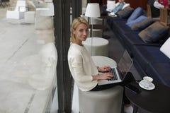 Giovane donna splendida che si siede con il computer portatile aperto nell'interno moderno dell'hotel o della caffetteria Immagine Stock