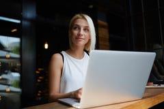Giovane donna splendida con il fronte grazioso che lavora al computer portatile mentre sedendosi nell'interno moderno della caffe Fotografia Stock