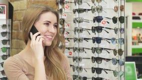 Giovane donna splendida felice che parla sul telefono mentre occhiali di compera immagine stock