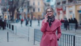 Giovane donna splendida in un cappotto rosa elegante che sta nel centro urbano, parlante felicemente sul telefono Via ammucchiata video d archivio