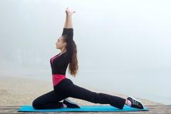 Giovane donna sportiva che allunga durante l'allenamento di addestramento all'aperto Fotografia Stock Libera da Diritti