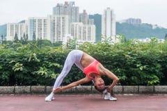 Giovane donna sportiva che allunga facendo posa del triangolo di yoga che sta nella posizione ampio-fornita di gambe che piega pe fotografia stock