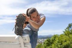 Giovane donna sportiva che allunga gamba all'aperto Immagine Stock