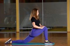 Giovane donna sportiva che allunga nella posizione di affondo della gamba in palestra Immagini Stock