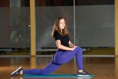 Giovane donna sportiva che allunga nella posizione di affondo della gamba in palestra Fotografia Stock