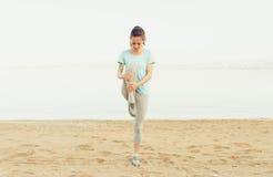 Giovane donna sportiva che allunga sulla spiaggia Immagini Stock