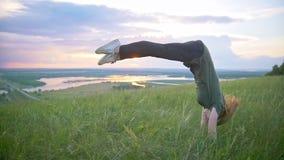 Giovane donna sportiva che esegue una vibrazione sull'erba al tramonto di estate stock footage