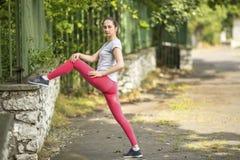 Giovane donna sportiva che fa allungamento e riscaldamento di esercizio prima di pareggiare nel parco in sole il bello giorno di  Immagini Stock Libere da Diritti