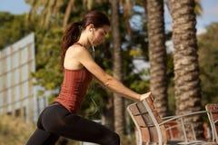 Giovane donna sportiva che fa allungando allenamento da un banco di parco all'aperto Fotografia Stock Libera da Diritti