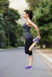 Giovane donna sportiva che fa allungando esercizio all'aperto Fotografia Stock