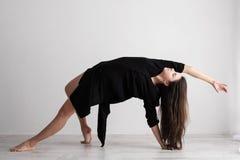 Giovane donna sportiva che fa pratica di yoga su fondo bianco - concetto di vita sana e di equilibrio naturale fra il corpo immagini stock