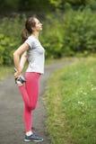 Giovane donna sportiva che fa riscaldamento di esercizio prima del pareggiare nel parco in sole il bello giorno di estate Immagini Stock