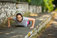 Giovane donna sportiva che fa spinta-UPS in parco in sole il bello giorno di estate Fotografia Stock Libera da Diritti