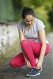 Giovane donna sportiva che lega i pizzi di scarpa da corsa in parco nel bello giorno di estate Fotografia Stock Libera da Diritti