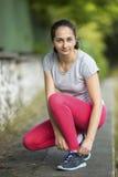 Giovane donna sportiva che lega i pizzi di scarpa da corsa prima del pareggiare nel parco in sole il bello giorno di estate Immagine Stock