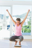 Giovane donna sportiva che si accovaccia sulla bilancia in palestra Fotografia Stock