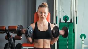 Giovane donna sportiva che si esercita con le teste di legno nella palestra video d archivio