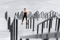 Giovane donna sportiva che si esercita e che allunga sulle scale dello stadio Immagine Stock Libera da Diritti
