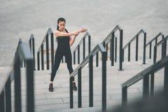 Giovane donna sportiva che si esercita e che allunga sulle scale dello stadio Immagine Stock