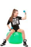 Giovane donna sportiva che si siede sul fitball con le teste di legno sulle sedere bianche Fotografia Stock