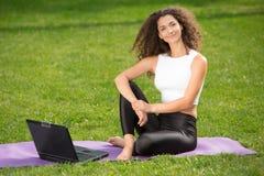 Giovane donna sportiva che si siede sull'erba con Fotografie Stock Libere da Diritti