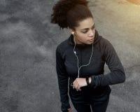 Giovane donna sportiva con l'inseguitore di forma fisica Immagini Stock Libere da Diritti