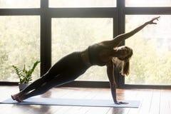 Giovane donna sportiva di forma fisica che fa esercizio di Vasisthasana fotografie stock libere da diritti