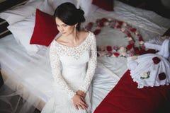 Giovane donna, sposa in hotel che si siede sul letto fotografia stock libera da diritti