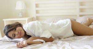 Giovane donna stanca attraente che si rilassa sul suo letto video d archivio