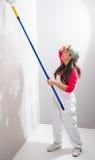 Giovane donna stanca che dipinge una parete immagini stock libere da diritti