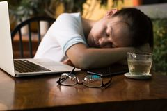 Giovane donna stanca che dorme sul suo scrittorio del computer immagini stock libere da diritti