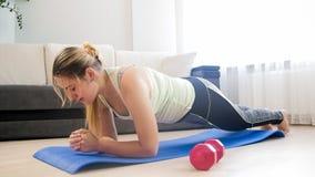 Giovane donna stanca che fa esercizio della plancia sulla stuoia di forma fisica a casa Fotografie Stock