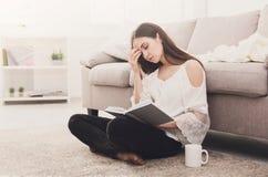 Giovane donna stanca che legge un libro Fotografia Stock