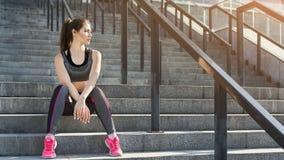 Giovane donna stanca che si rilassa sulle scale fotografia stock