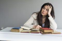 giovane donna stanca che si siede al suo scrittorio con i libri nella parte anteriore Fotografie Stock Libere da Diritti