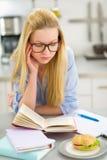Giovane donna stanca che studia nella cucina Immagine Stock Libera da Diritti
