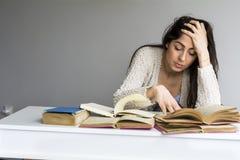 Giovane donna stanca con l'emicrania che studia per gli esami Immagine Stock Libera da Diritti