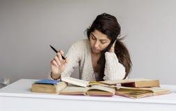 Giovane donna stanca con l'emicrania che studia per gli esami Fotografie Stock Libere da Diritti