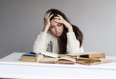 Giovane donna stanca con l'emicrania che studia per gli esami Immagini Stock