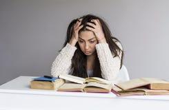 Giovane donna stanca con l'emicrania che studia per gli esami Fotografia Stock Libera da Diritti