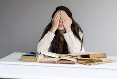 Giovane donna stanca con l'emicrania che studia per gli esami Immagini Stock Libere da Diritti