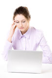 Giovane donna stanca con lo sguardo annoiato davanti al computer portatile Fotografia Stock