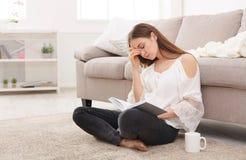 Giovane donna stanca con un libro Immagini Stock Libere da Diritti